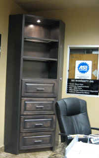 Custm corner hutch with lit glass shelving and hanging folder drawers for display and organization.