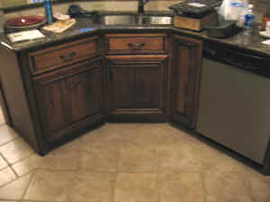 Diagonal sink cabinet next to trash drawer and dishwasher in Island