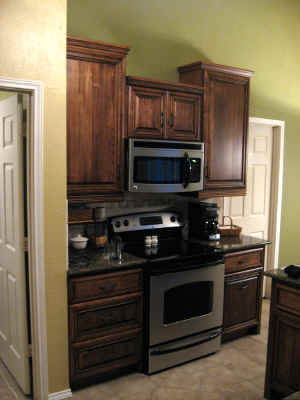 Cooking area with range. 42 inch upper cabinets create tower effect and add interest.